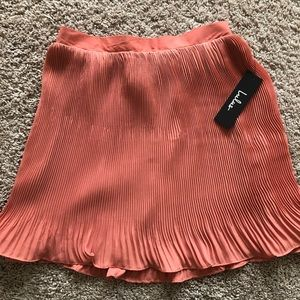Pink pleated mini skirt. Never worn-with tags!